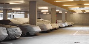 covered cars lined up in a car garage